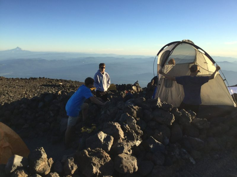 Setting up tent in rock ring at Lunch Counter on Mt. Adams with Mt. Hood in background